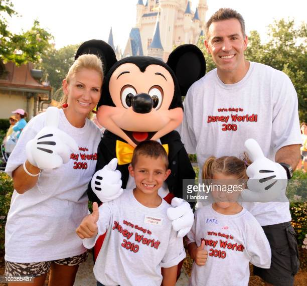 In this handout image provided by Disney retired NFL quarterback Kurt Warner poses with his wife Brenda Warner Mickey Mouse and and Dakota and Kate...