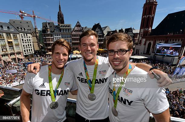 In this handout image provided by DOSB German olympic athletes Richard Schmidt Andreas Kuffner and Eric Johannesen pose at the Roemerberg on August...