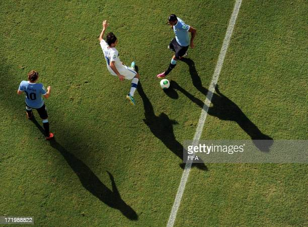 In this handout image provided by FIFA Alvaro Pereira of Uruguay competes with Alberto Aquilani of Italy during the FIFA Confederations Cup Brazil...