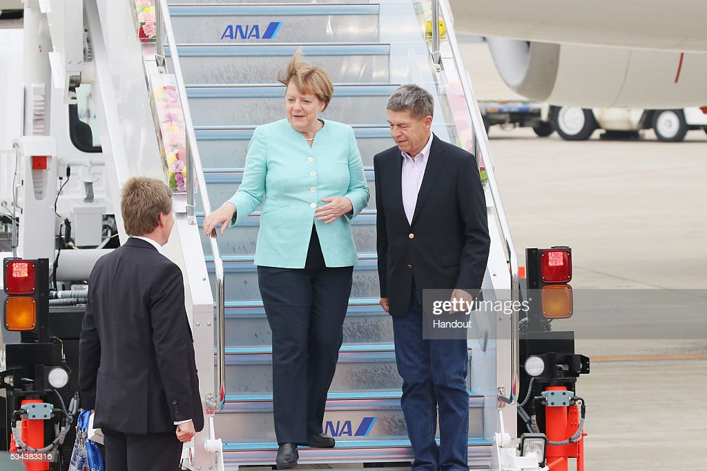 In this handout image provided by Foreign Ministry of Japan, German Chancellor <a gi-track='captionPersonalityLinkClicked' href=/galleries/search?phrase=Angela+Merkel&family=editorial&specificpeople=202161 ng-click='$event.stopPropagation()'>Angela Merkel</a> (L) and husband <a gi-track='captionPersonalityLinkClicked' href=/galleries/search?phrase=Joachim+Sauer&family=editorial&specificpeople=687595 ng-click='$event.stopPropagation()'>Joachim Sauer</a> (R) are seen upon arrival at the Chubu Centrair International Airport on May 26, 2016 in Nagoya, Japan. In the two-day summit held on May 26 and 27, the G7 leaders are scheduled to discuss the pressing global issues including counter-terrorism, energy policy, and sustainable development.
