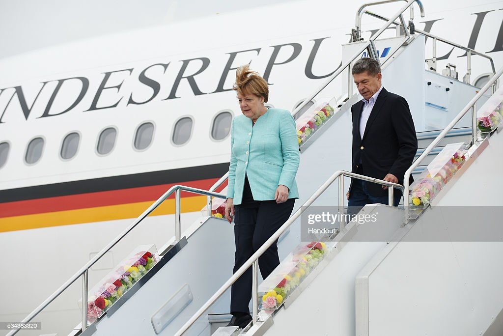 In this handout image provided by Foreign Ministry of Japan German Chancellor Angela Merkel and husband Joachim Sauer are seen upon arrival at the...