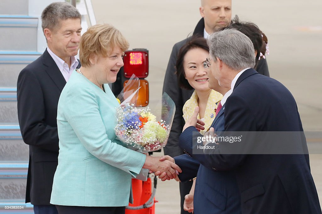 In this handout image provided by Foreign Ministry of Japan, German Chancellor Angela Merkel (2nd from L) and husband <a gi-track='captionPersonalityLinkClicked' href=/galleries/search?phrase=Joachim+Sauer&family=editorial&specificpeople=687595 ng-click='$event.stopPropagation()'>Joachim Sauer</a> (L) are seen welcomed upon arrival at the Chubu Centrair International Airport on May 26, 2016 in Nagoya, Japan. In the two-day summit held on May 26 and 27, the G7 leaders are scheduled to discuss the pressing global issues including counter-terrorism, energy policy, and sustainable development.