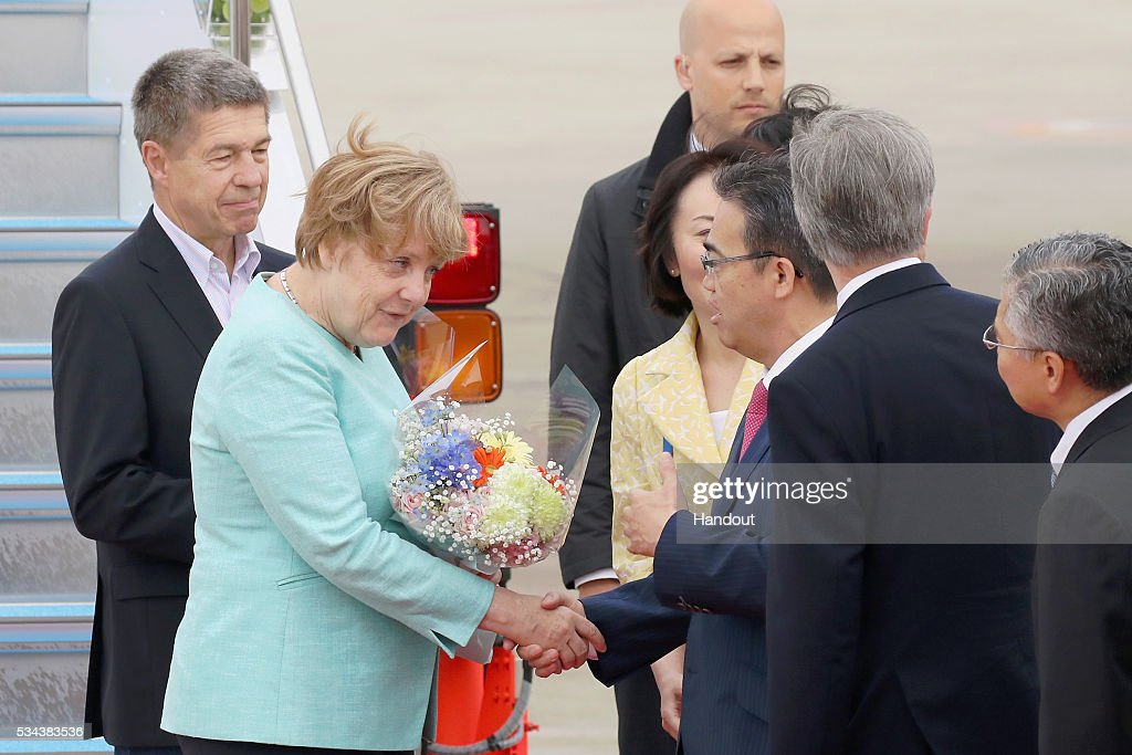 In this handout image provided by Foreign Ministry of Japan German Chancellor Angela Merkel and husband Joachim Sauer are seen welcomed upon arrival...