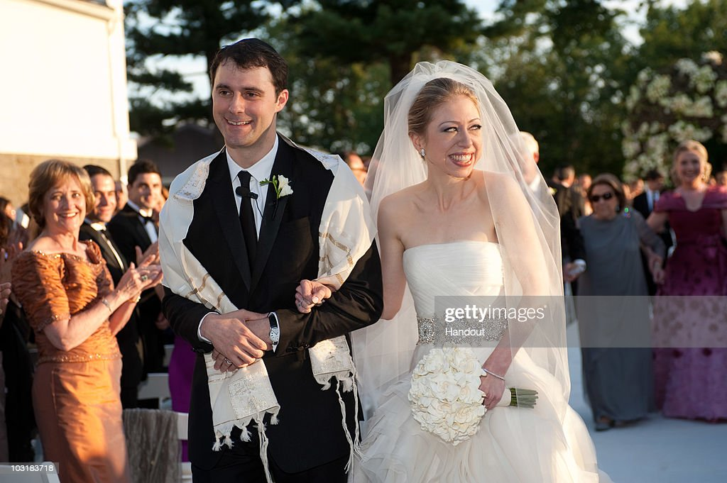 In this handout image provided by Genevieve de Manio, Chelsea Clinton (R) weds Marc Mezvinsky at the Astor Courts Estate on July 31, 2010 in Rhinebeck, New York. Chelsea Clinton, the daughter of former U.S. President Bill Clinton and Secretary of State Hillary Clinton, married Marc Mezvinsky today in an interfaith ceremony at the estate built by John Jacob Astor on the Hudson River about two hours north of New York City.