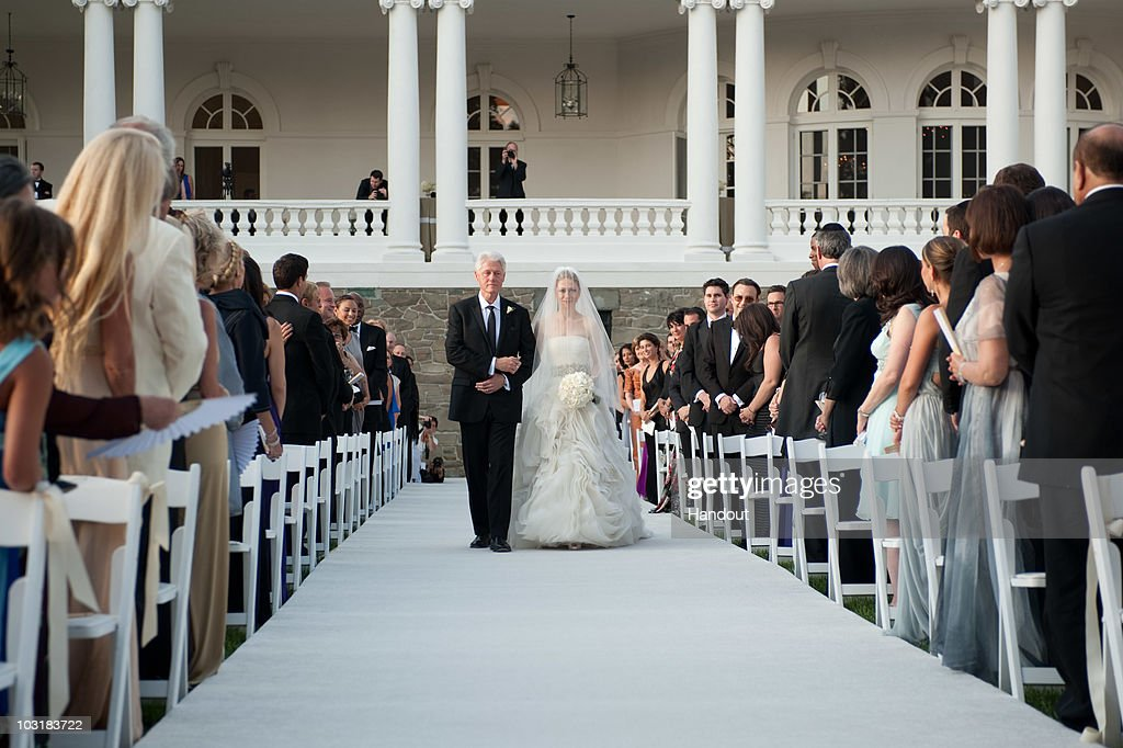 In this handout image provided by Genevieve de Manio, former U.S. President Bill Clinton (L) walks Chelsea Clinton down the aisle during her wedding to Marc Mezvinsky at the Astor Courts Estate on July 31, 2010 in Rhinebeck, New York. Chelsea Clinton, the daughter of former U.S. President Bill Clinton and Secretary of State Hillary Clinton, married Marc Mezvinsky today in an interfaith ceremony at the estate built by John Jacob Astor on the Hudson River about two hours north of New York City.
