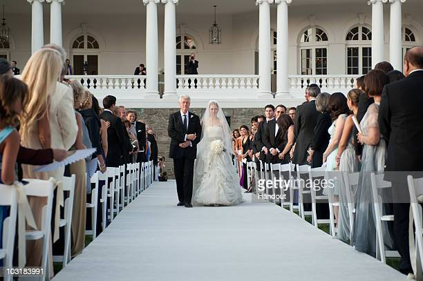 In this handout image provided by Genevieve de Manio former US President Bill Clinton walks Chelsea Clinton down the aisle during her wedding to Marc...