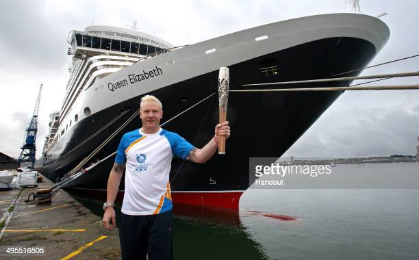 In this handout image provided by Glasgow 2014 Ltd Baton bearer Iwan Thomas holds the Queen's Baton in front of Cunard's Queen Elizabeth ship as the...