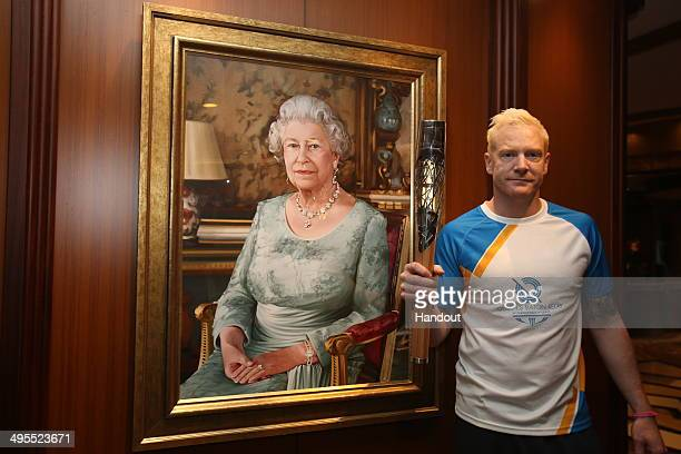 In this handout image provided by Glasgow 2014 Ltd Baton bearer Iwan Thomas holds the Queen's Baton in front of a portrait of Queen Elizabeth II...