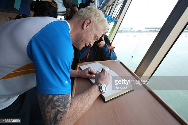 In this handout image provided by Glasgow 2014 Ltd Baton bearer Iwan Thomas signs a book aboard Cunard's Queen Elizabeth ship as the Glasgow 2014...