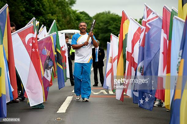 In this handout image provided by Glasgow 2014 Ltd Batonbearer 001 Daley Thompson carries the Glasgow 2014 Queen's Baton across the bridge at...