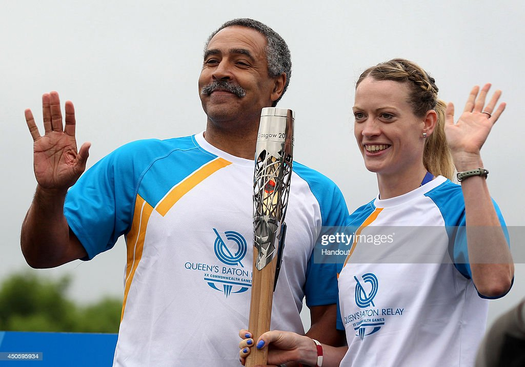 In this handout image provided by Glasgow 2014 Ltd, Batonbearer 001 <a gi-track='captionPersonalityLinkClicked' href=/galleries/search?phrase=Daley+Thompson&family=editorial&specificpeople=228442 ng-click='$event.stopPropagation()'>Daley Thompson</a> (L) hands the Glasgow 2014 Queen's Baton to Scottish athlete batonbearer 002 <a gi-track='captionPersonalityLinkClicked' href=/galleries/search?phrase=Eilidh+Child&family=editorial&specificpeople=6146746 ng-click='$event.stopPropagation()'>Eilidh Child</a> on the bridge at Coldstream as the baton crosses from England to Scotland on June 14, 2014 in Coldstream, Scotland. England is nation 69 of 70 nations and territories the Queen's Baton will visit.