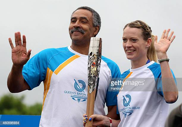In this handout image provided by Glasgow 2014 Ltd Batonbearer 001 Daley Thompson hands the Glasgow 2014 Queen's Baton to Scottish athlete...