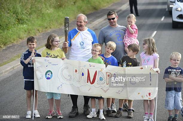In this handout image provided by Glasgow 2014 Ltd Batonbearer 001 Peter Gallagher carries the Glasgow 2014 Queen's Baton through Duns in the...