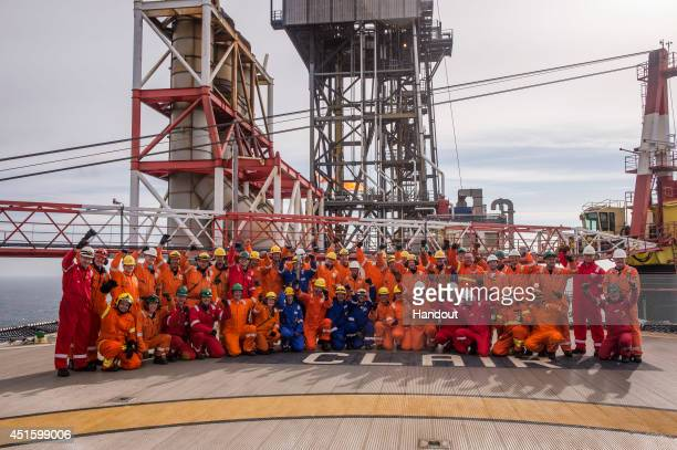 In this handout image provided by Glasgow 2014 Ltd Batonbearer 001 Christopher Hill carries the Glasgow 2014 Queen's Baton through Clair Oil Platform...