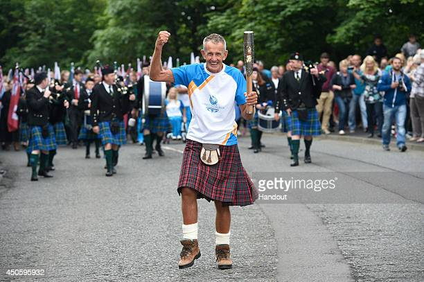 In this handout image provided by Glasgow 2014 Ltd Batonbearer 004 David Laing carries the Glasgow 2014 Queen's Baton through Coldstream in the...
