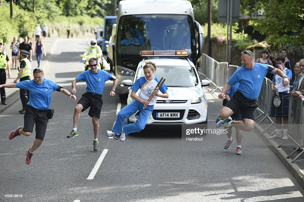 In this handout image provided by Glasgow 2014 Ltd, Batonbearer 010 Kirsty Millar carries the Glasgow 2014 Queen's Baton through Duns in the Scottish Borders during the Glasgow 2014 Queen's Baton relay on June 18, 2014 in Duns, Scotland. Scotalnd is nation 70 of 70 nations and territories the Queen's Baton will visit.