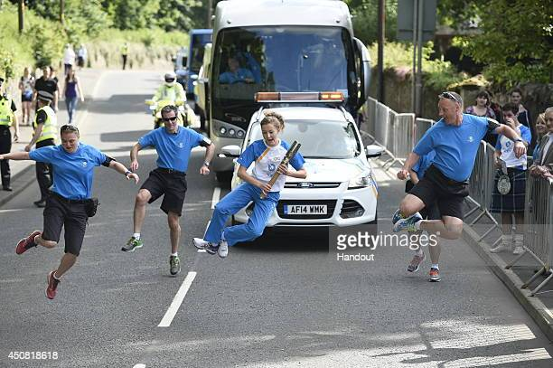 In this handout image provided by Glasgow 2014 Ltd Batonbearer 010 Kirsty Millar carries the Glasgow 2014 Queen's Baton through Duns in the Scottish...