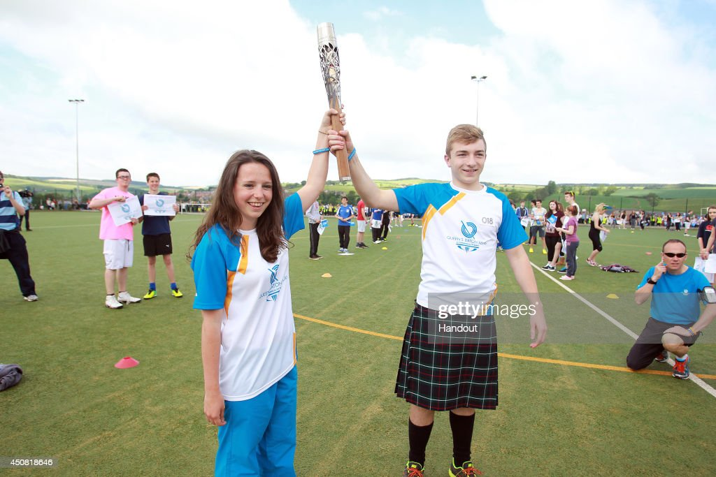 In this handout image provided by Glasgow 2014 Ltd, Batonbearer 018 Callum Love hands the Glasgow 2014 Queen's Baton to Batonbearer 019 Jennifer Bond through Earlston in the Scottish Borders during the Glasgow 2014 Queen's Baton relay on June 18, 2014 in Earlston, Scotland. Scotalnd is nation 70 of 70 nations and territories the Queen's Baton will visit.