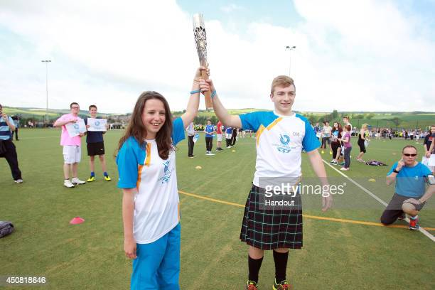In this handout image provided by Glasgow 2014 Ltd Batonbearer 018 Callum Love hands the Glasgow 2014 Queen's Baton to Batonbearer 019 Jennifer Bond...