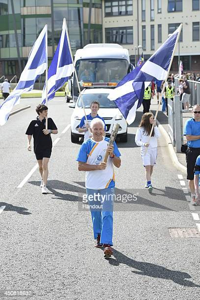 In this handout image provided by Glasgow 2014 Ltd Batonbearer 020 Alexander Gilchrist carries the Glasgow 2014 Queen's Baton through Earlston in the...