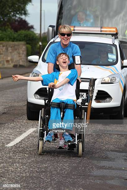 In this handout image provided by Glasgow 2014 Ltd Batonbearer 023 Sean McCann carries the Glasgow 2014 Queen's Baton through Musselburgh in East...