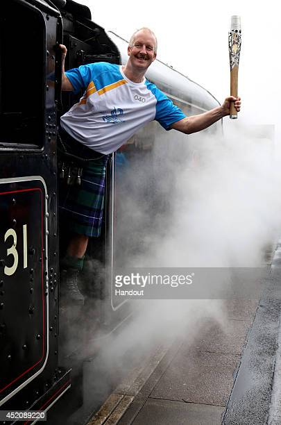 In this handout image provided by Glasgow 2014 Ltd Batonbearer 040 David Sedgwick carries the Glasgow 2014 Queen's Baton as he boards a train at...
