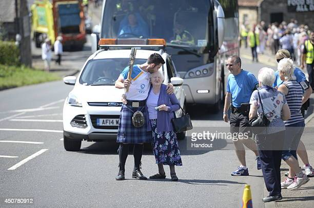 In this handout image provided by Glasgow 2014 Ltd Batonbearer 056 Paul Van Rietvelde carries the Glasgow 2014 Queen's Baton through Longniddry in...