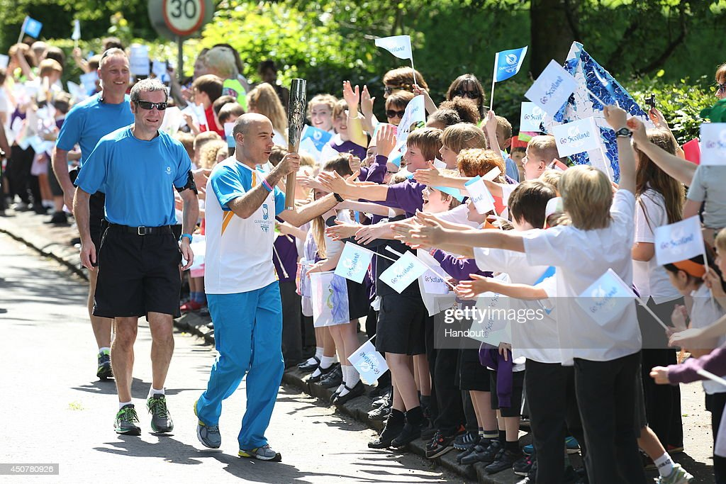In this handout image provided by Glasgow 2014 Ltd, Batonbearer 058 John Moos carries the Glasgow 2014 Queen's Baton through Longniddry in East Lothian during the Glasgow 2014 Queen's Baton relay on June 17, 2014 in East Lothian, Scotland. Scotalnd is nation 70 of 70 nations and territories the Queen's Baton will visit.
