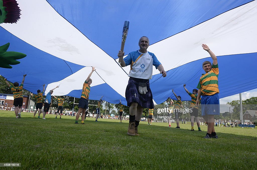 In this handout image provided by Glasgow 2014 Ltd, Batonbearer 058 Allan McGee carries the Glasgow 2014 Queen's Baton at Selkirk Rugby Football Club in the Scottish Borders during the Glasgow 2014 Queen's Baton relay on June 18, 2014 in Selkirk, Scotland. Scotalnd is nation 70 of 70 nations and territories the Queen's Baton will visit.