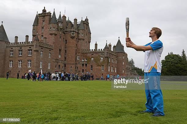 In this handout image provided by Glasgow 2014 Ltd Batonbearer 061 Stewart Watson carries the Glasgow 2014 Queen's Baton at Glamis Castle Angus...