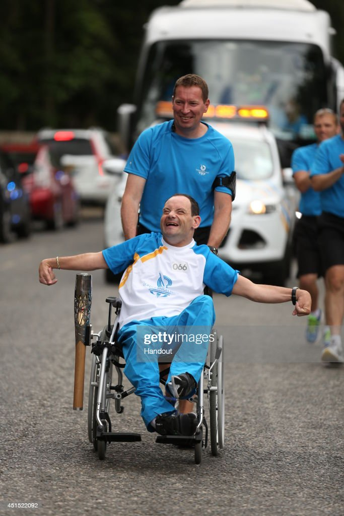 In this handout image provided by Glasgow 2014 Ltd, Batonbearer 066 Callum McDougall carries the Glasgow 2014 Queen's Baton through Garthdee in Aberdeen during the Glasgow 2014 Queen's Baton relay on June 30, 2014 in Garthdee, Scotland. Scotland is nation 70 of 70 nations and territories the Queen's Baton will visit.