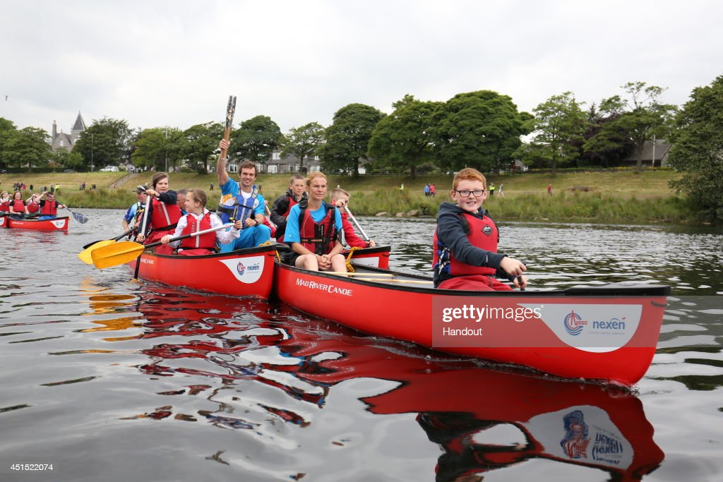 In this handout image provided by Glasgow 2014 Ltd, Batonbearer 078 Timothy Baillie, Scottish slalom canoer, carries the Glasgow 2014 Queen's Baton in a canoe on the River Dee in Aberdeen during the Glasgow 2014 Queen's Baton relay on June 30, 2014 in Aberdeen, Scotland. Scotland is nation 70 of 70 nations and territories the Queen's Baton will visit.
