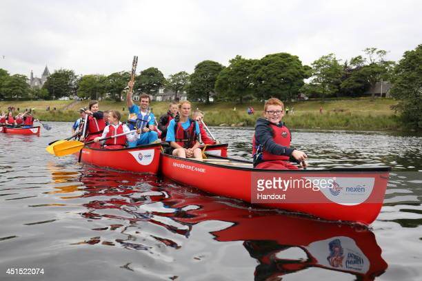 In this handout image provided by Glasgow 2014 Ltd Batonbearer 078 Timothy Baillie Scottish slalom canoer carries the Glasgow 2014 Queen's Baton in a...