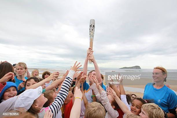 In this handout image provided by Glasgow 2014 Ltd Batonbearer 081 Morna Renwick holds aloft the Glasgow 2014 Queen's Baton through North Berwick in...