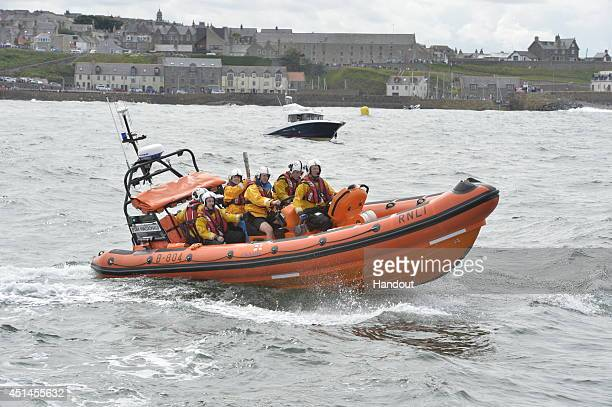 In this handout image provided by Glasgow 2014 Ltd Batonbearer 090 Kay Copland carries the Glasgow 2014 Queen's Baton on a lifeboat in Banff Bay...