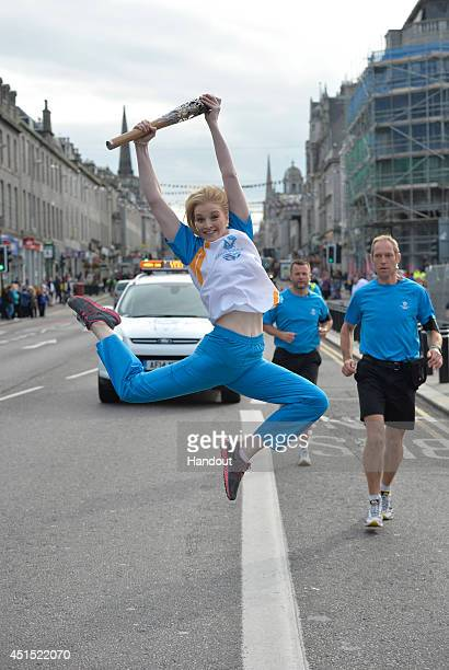 In this handout image provided by Glasgow 2014 Ltd Batonbearer 117 Scottish rhythmic gymnastics champion Rebecca Bee carries the Glasgow 2014 Queen's...