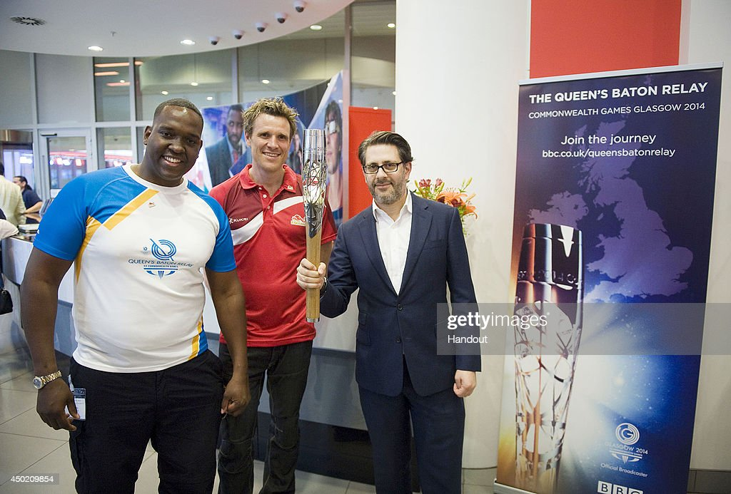 In this handout image provided by Glasgow 2014 Ltd BMX Ambassador Michael Pusey and James Cracknell hand over the Queen's Baton to Director of BBC...