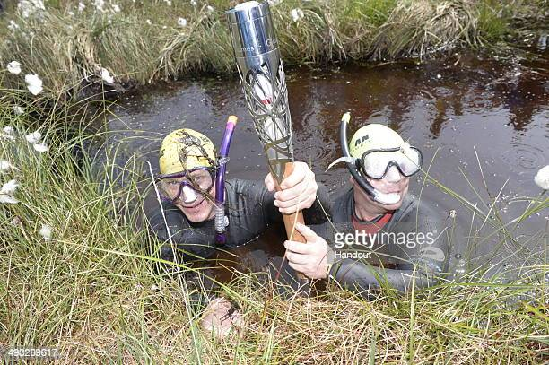 In this handout image provided by Glasgow 2014 Ltd Bog snorkelers with the Commonwealth Games Baton at Peatlands Park during the Glasgow 2014 Baton...