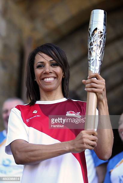 In this handout image provided by Glasgow 2014 Ltd Dame Kelly Holmes holds the Queen's Baton in front of Tonbridge Castle as the Glasgow 2014 Queen's...