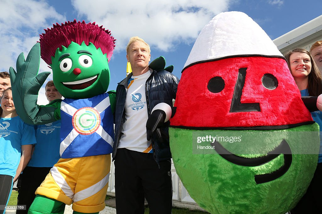 In this handout image provided by Glasgow 2014 Ltd, Former Welsh athlete Iwan Thomas holds the Queen's Baton as he poses with Glasgow 2014 mascot Clyde and Mr Urdd, mascot for the annual Welsh language youth festival of literature, music and performing arts and local schoolchildren during the Glasgow 2014 Baton Relay on May 26, 2014 in Eisteddfod, Wales. Wales is nation 68 of 70 nations and territories the Queen's Baton will visit.