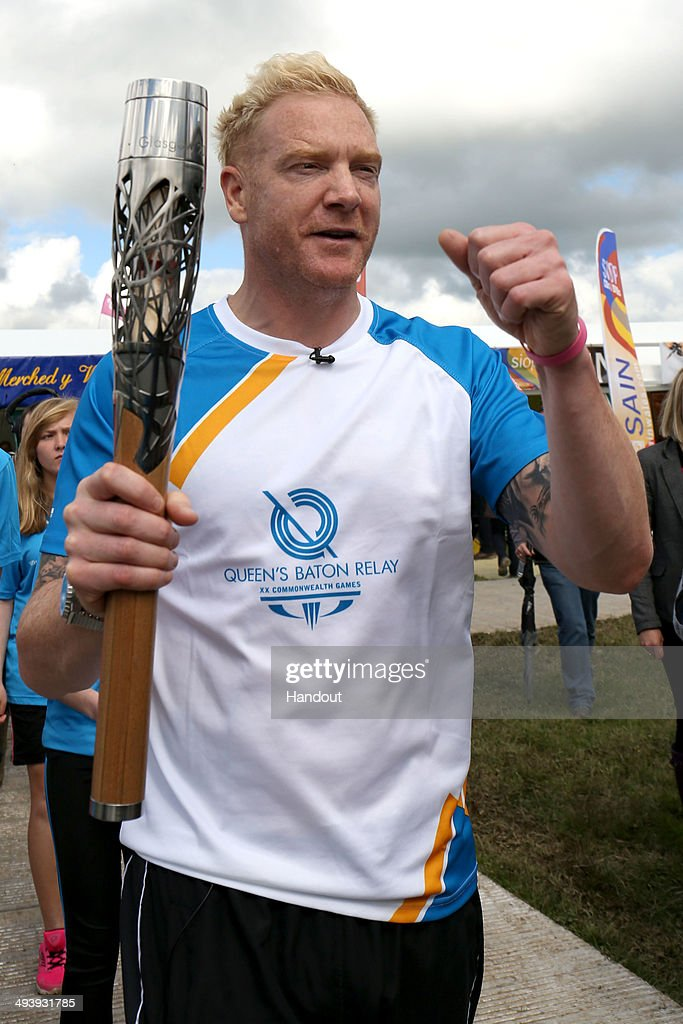 In this handout image provided by Glasgow 2014 Ltd, Former Welsh athlete Iwan Thomas holds the Queen's Baton during the Glasgow 2014 Baton Relay on May 26, 2014 in Eisteddfod, Wales. Wales is nation 68 of 70 nations and territories the Queen's Baton will visit.