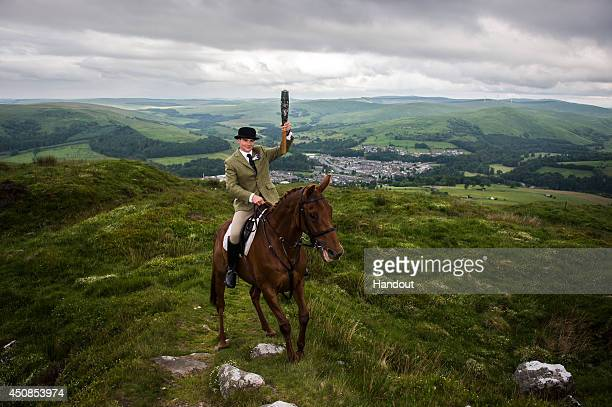In this handout image provided by Glasgow 2014 Ltd Riders from the Langholm Cornet relay the Queen's Baton in the hills surrounding Langolm in...