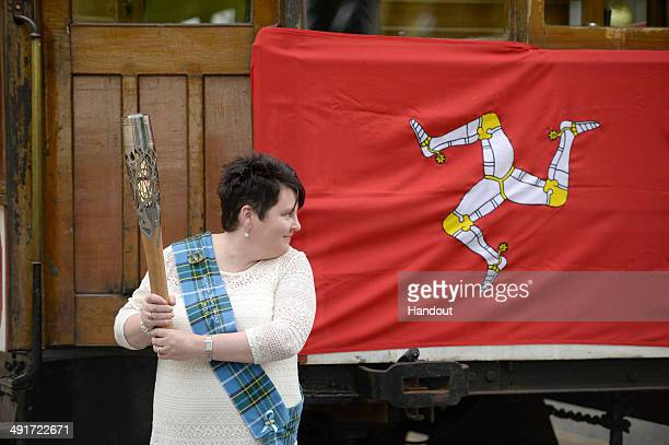 In this handout image provided by Glasgow 2014 Ltd Vicki Hewson holds the Commonwealth Games Baton in Laxey Village as it makes it's way around the...