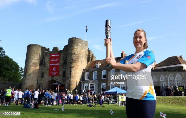 In this handout image provided by Glasgow 2014 Ltd Winter Olympic gold medalist Lizzy Yarnold holds the Queen's Baton in front of Tonbridge Castle as...