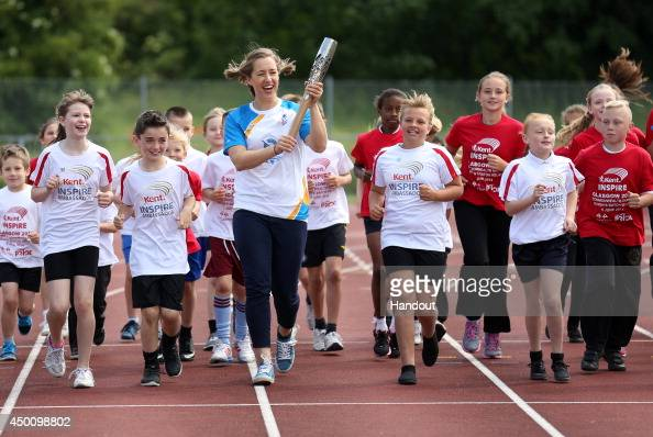 In this handout image provided by Glasgow 2014 Ltd Winter Olympic gold medalist Lizzy Yarnold holds the Queen's Baton at the Dartford Harriers Track...