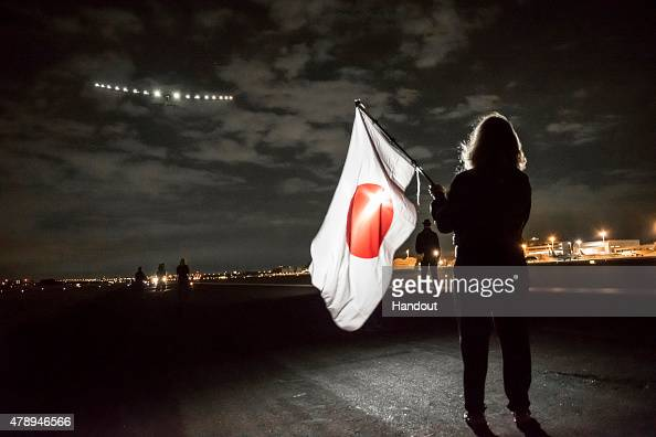 In this handout image provided by Global Newsroom picture shows Yasemine Borschberg waving a Japanese flag as Solar Impulse 2 a solar power plane is...