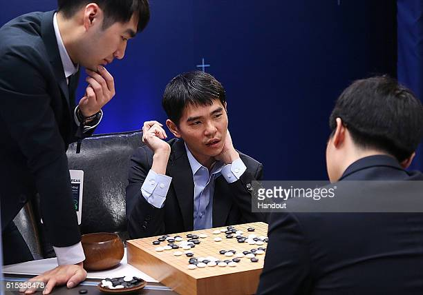 In this handout image provided by Google South Korean professional Go player Lee SeDol reviews the match with other professional Go players after the...
