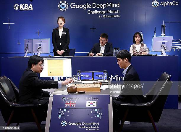 In this handout image provided by Google South Korean professional Go player Lee SeDol watches as Google DeepMind's lead programmer Aja Huang puts...