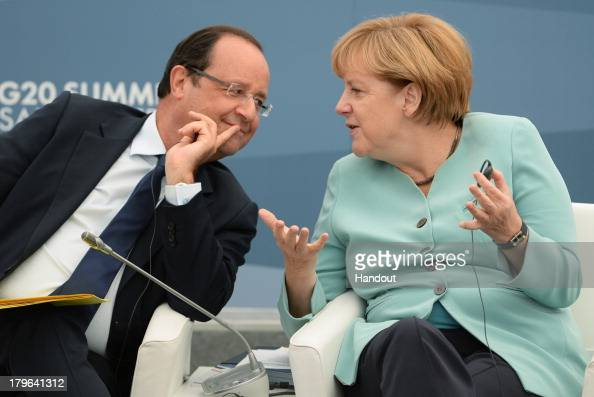 In this handout image provided by Host Photo Agency French President Francois Hollande and German Chancellor Angela Merkel attend a meeting with...