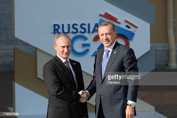 In this handout image provided by Host Photo Agency Russian President Vladimir Putin and Prime Minister of Turkey Recep Tayyip Erdogan shake hands...